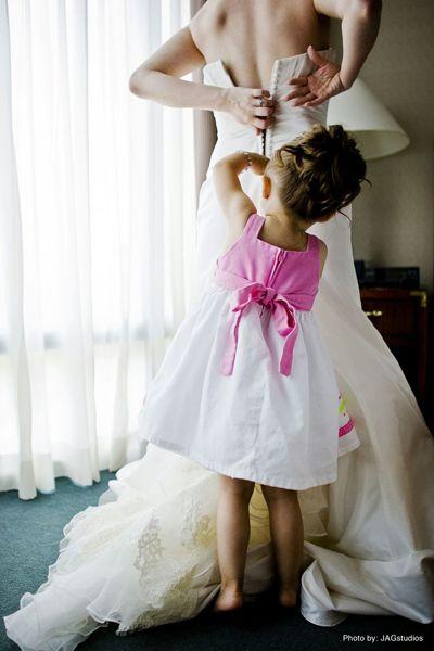 flowergirl helping bride get dressed